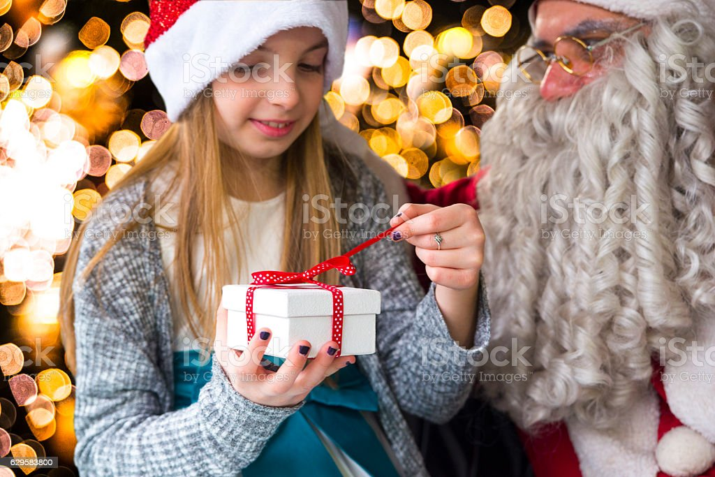 Little Girl with gift next to Santa Claus stock photo