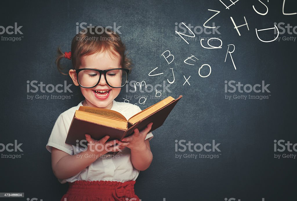 little girl with glasses reading a book with departing letters stock photo