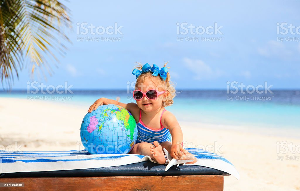 little girl with globe and toy plane on beach stock photo