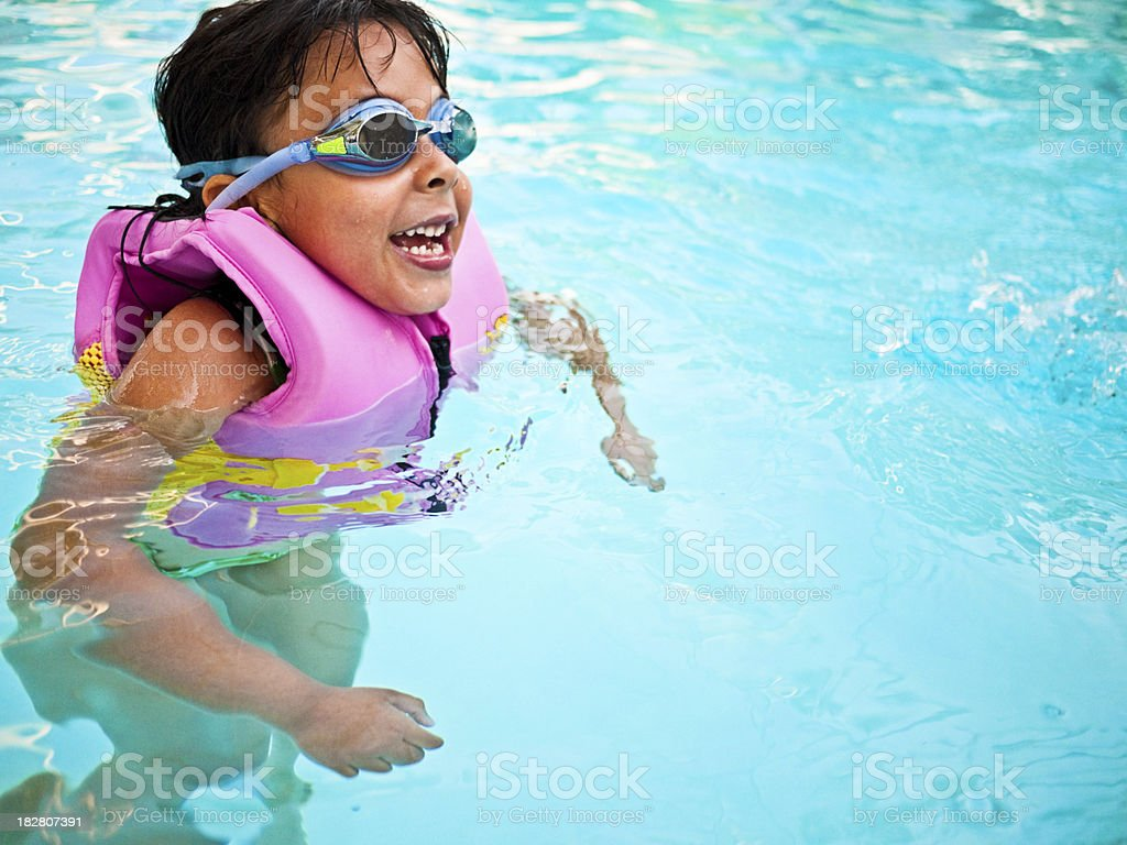little girl with goggles swimming stock photo