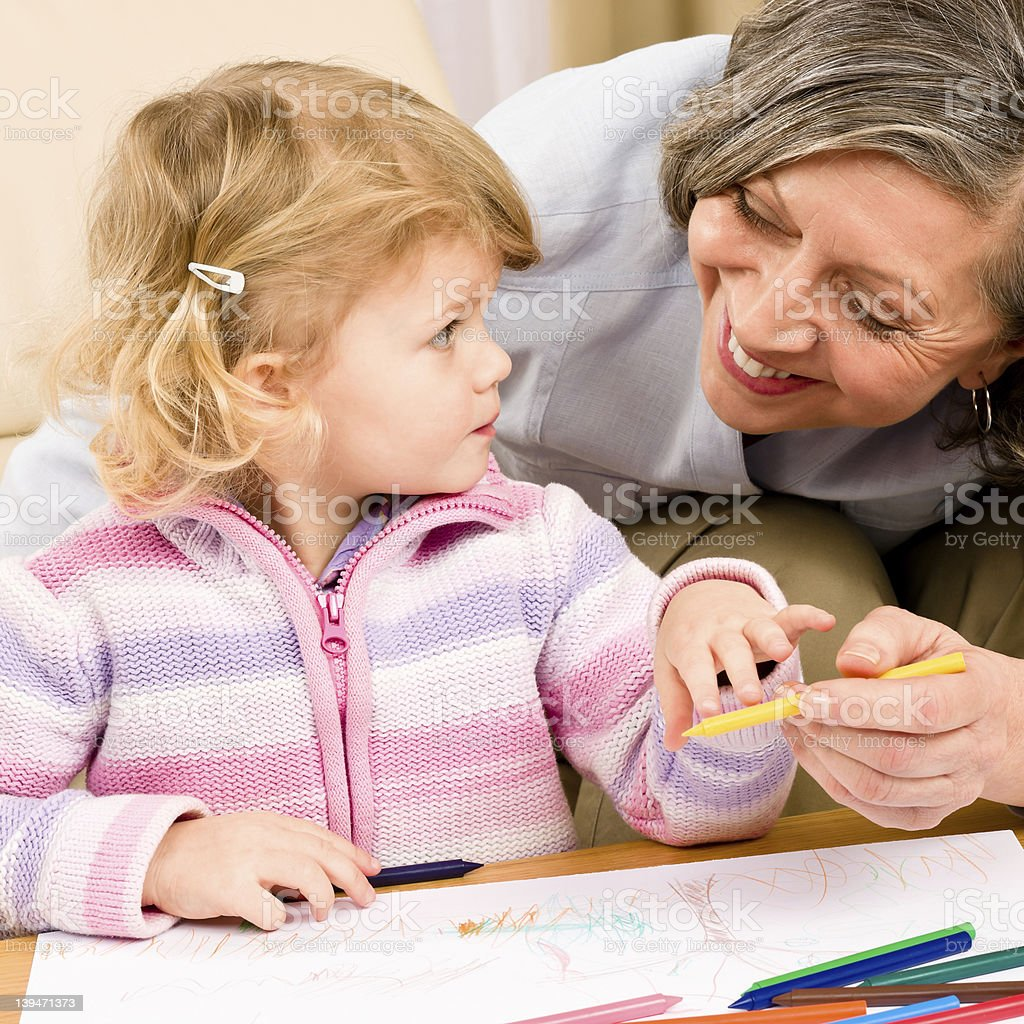Little girl with grandmother drawing together royalty-free stock photo