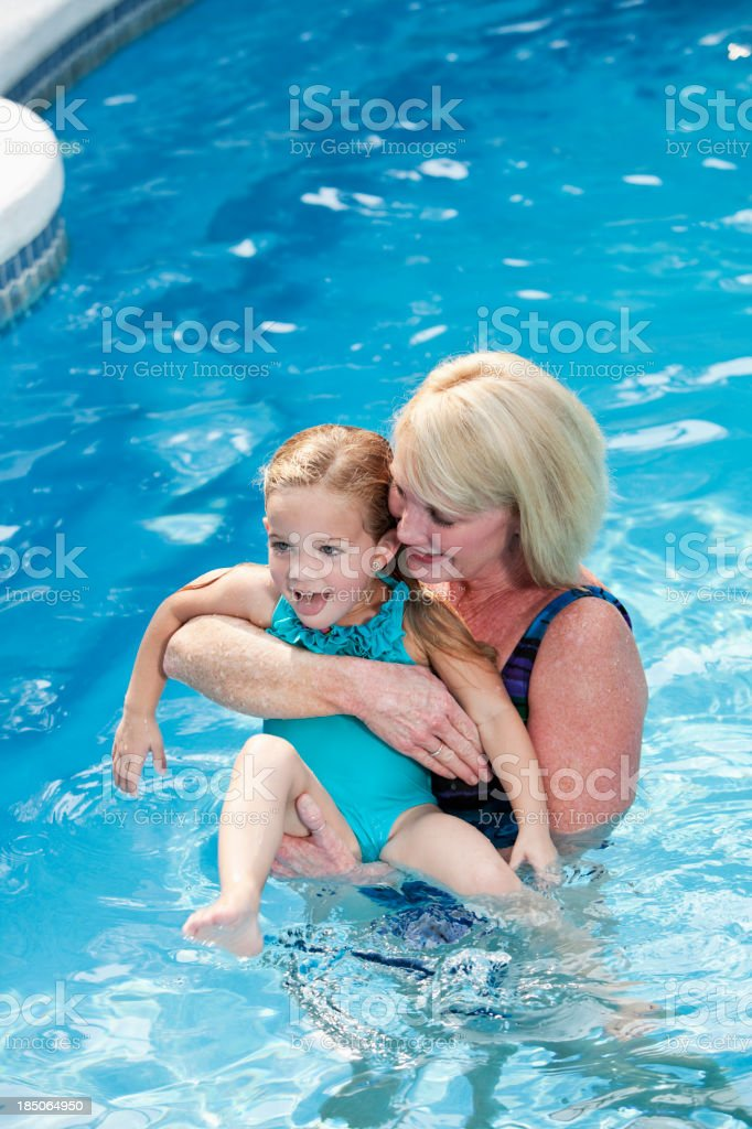 Little girl with grandmother in swimming pool stock photo