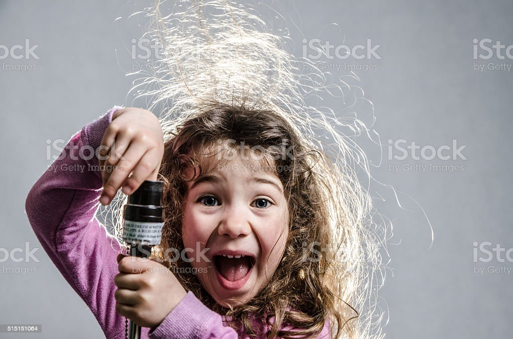 Little girl with hair electrified with finger in light socket stock photo