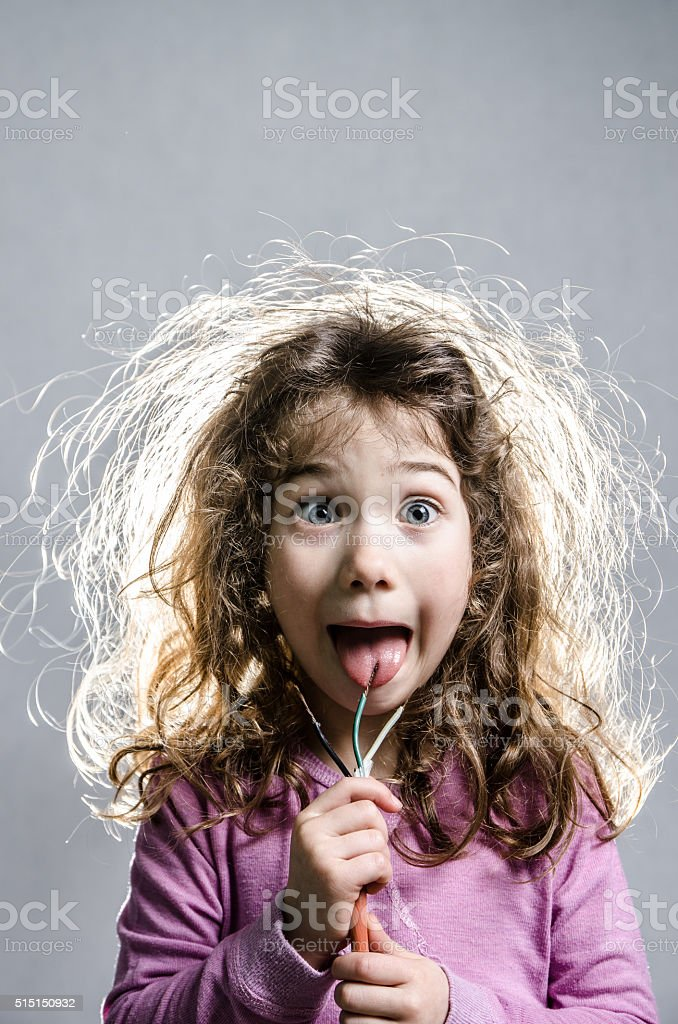 Little girl with hair electrified with tongue on wires stock photo