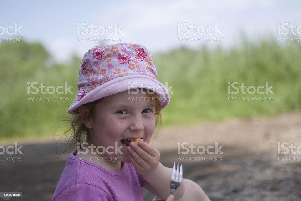 Little girl with hat, eating melon royalty-free stock photo