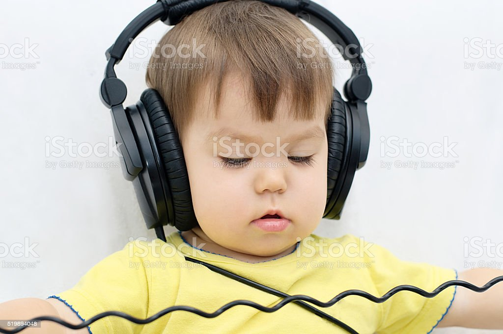Little girl with headphones playing stock photo