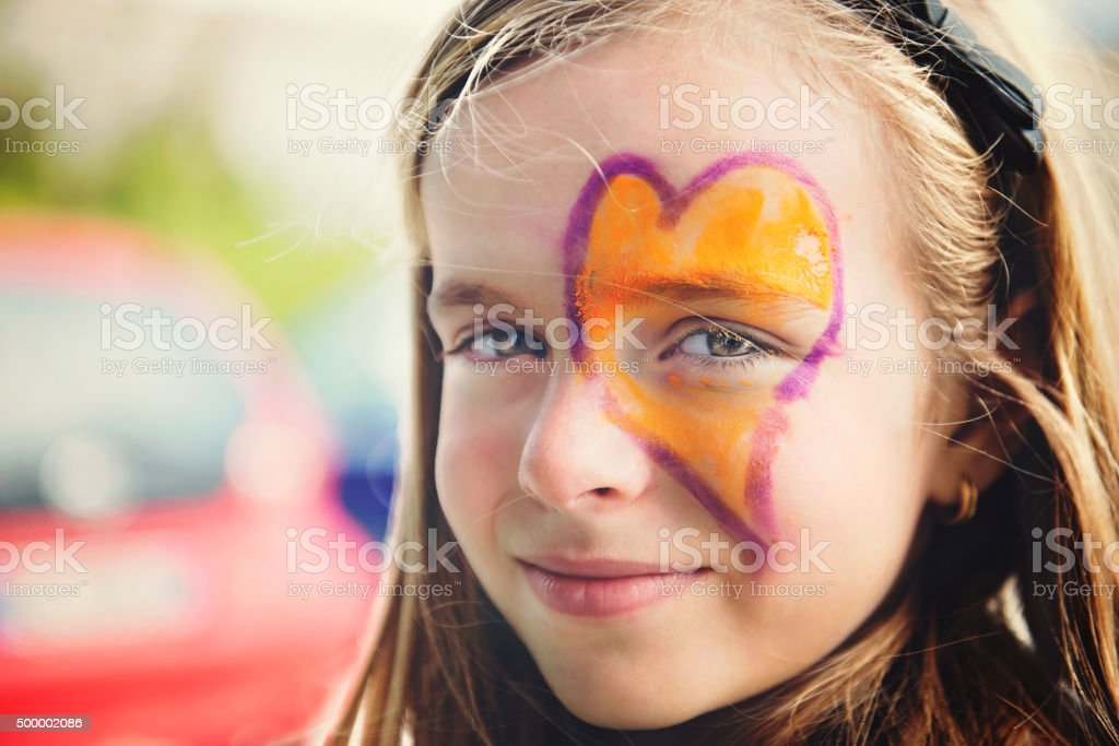 Little Girl with Heart Painted on the Face stock photo