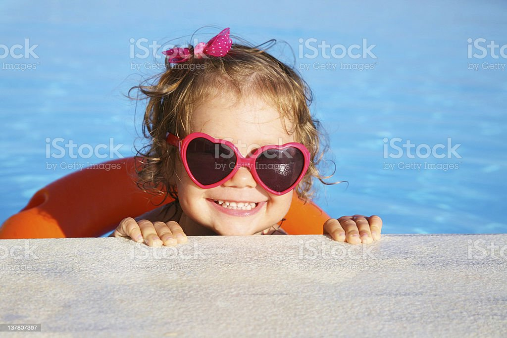 Little girl with heart-shaped sunglasses swimming in a pool stock photo