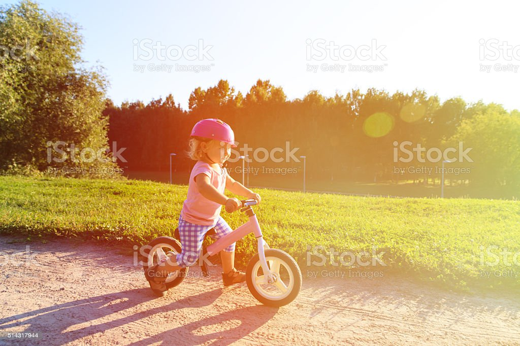 little girl with helmet riding bike at sunset stock photo