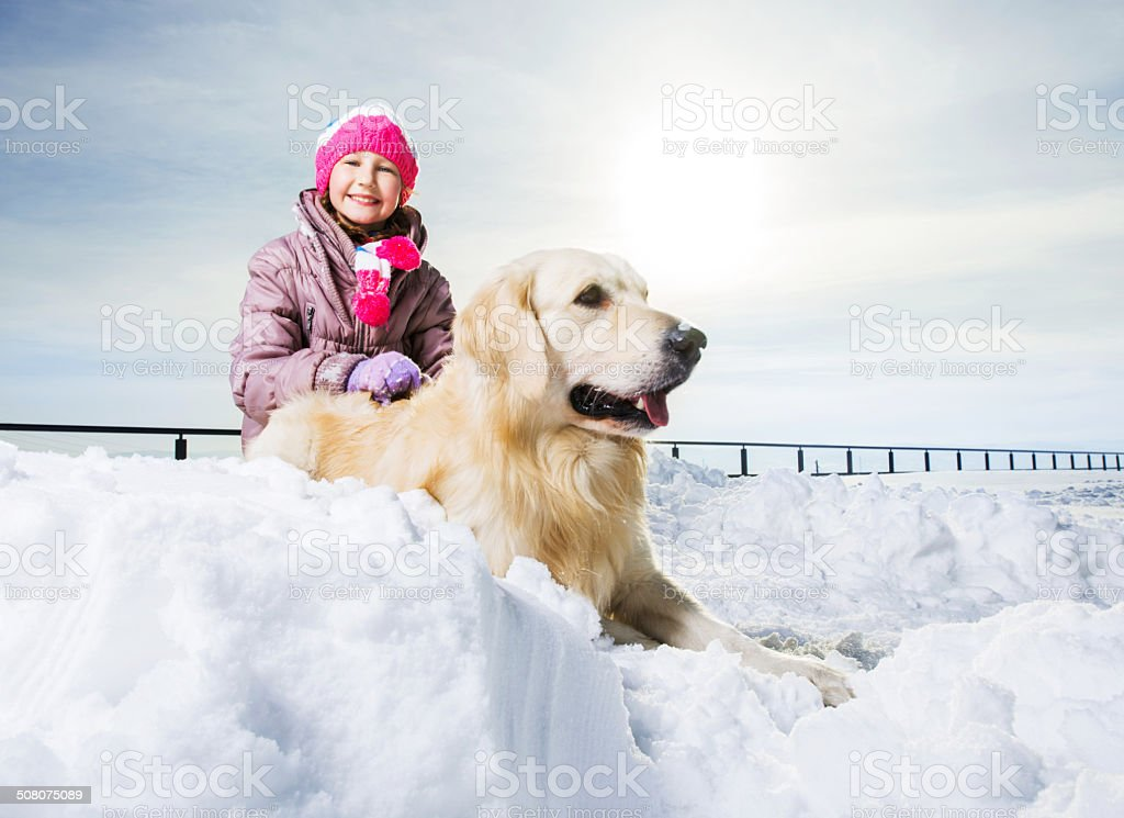 Little girl with her dog enjoying in snow. royalty-free stock photo