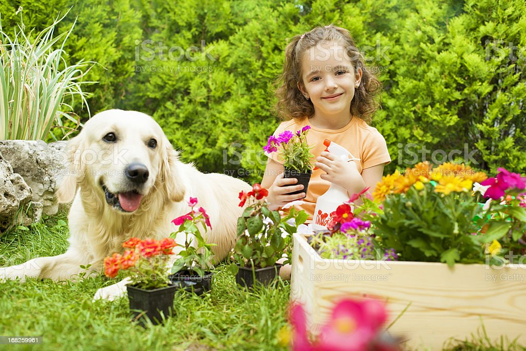 Little girl with her dog gardening. royalty-free stock photo