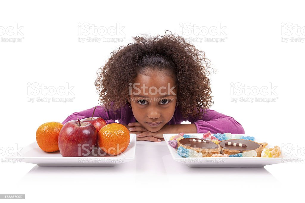 Little girl with her head on a table with fruits and candy royalty-free stock photo