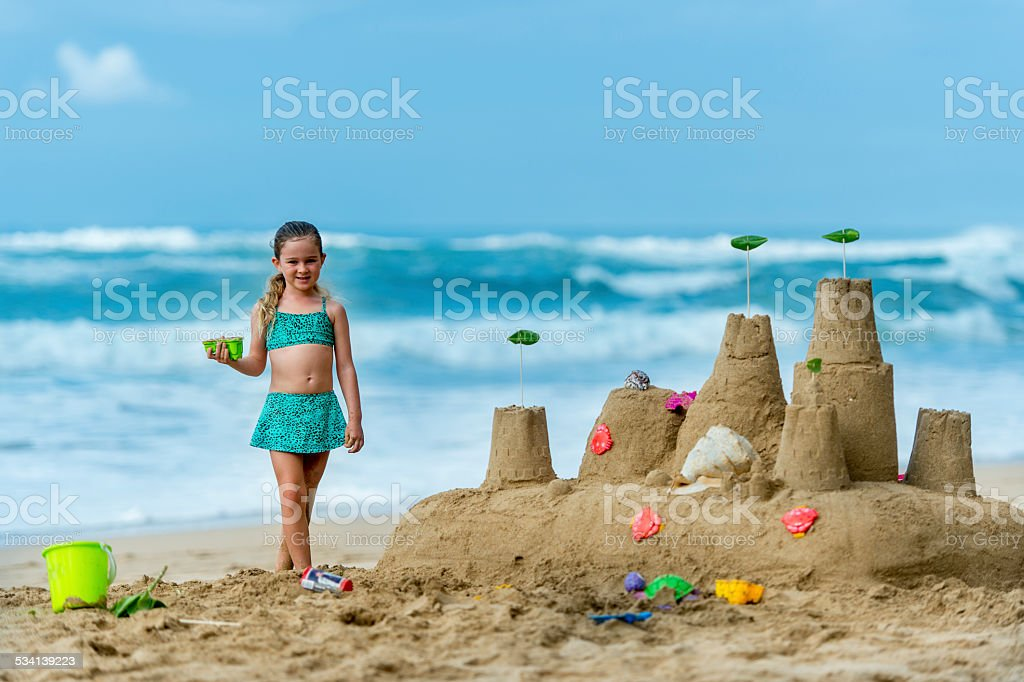 Little girl with her sand castle stock photo