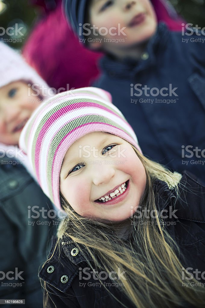 Little girl with his siblings behind her royalty-free stock photo