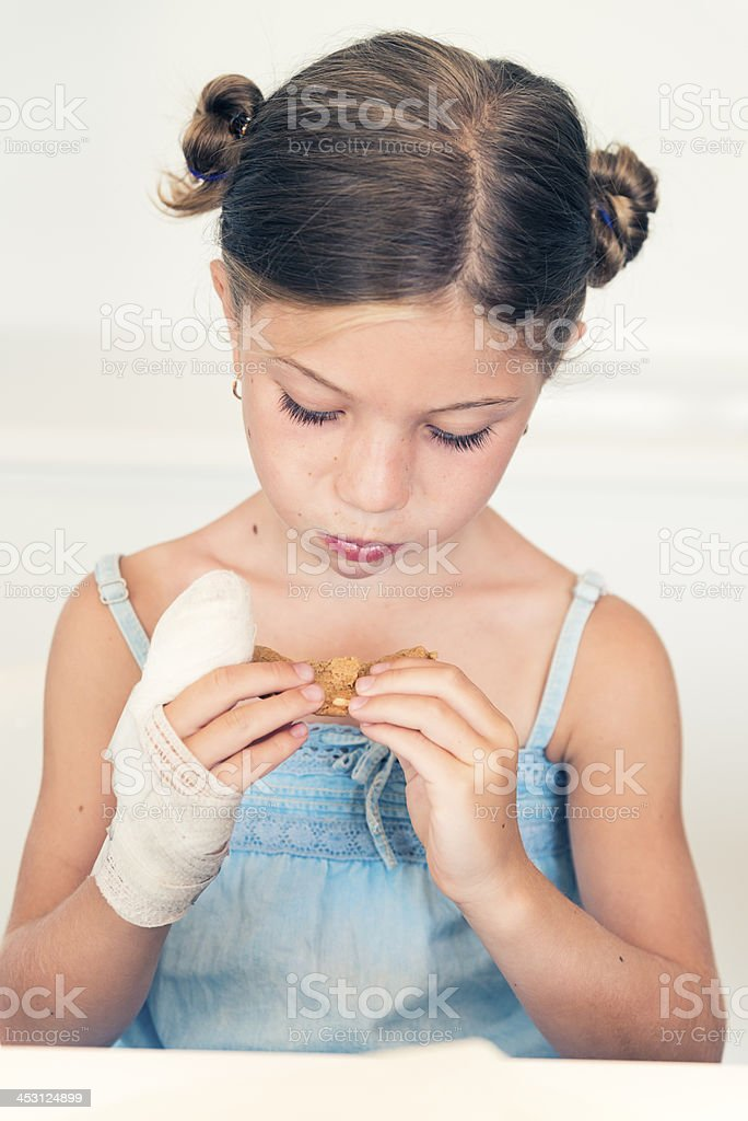 Little girl with injured hand in bandage eating cookie. royalty-free stock photo
