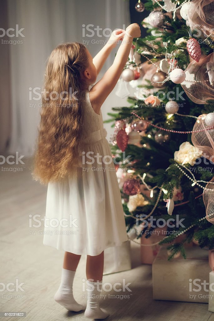 Little girl with long hair decorating christmas tree, vintage toned stock photo