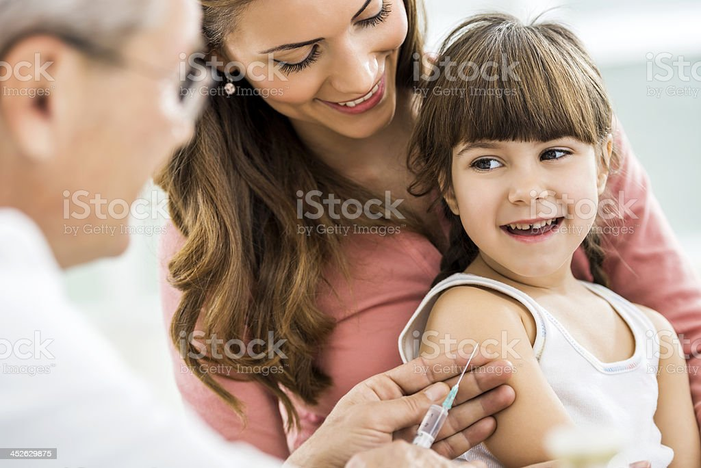 Little girl with mom, about to receive injection stock photo