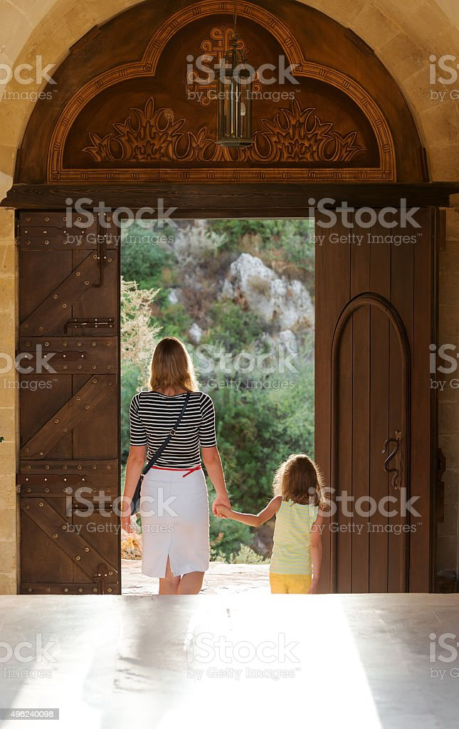 Little girl with mom leaving the Orthodox monastery. stock photo