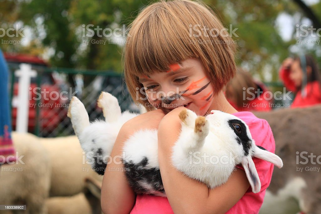 Little girl with painted tiger face holds rabbit upside down stock photo