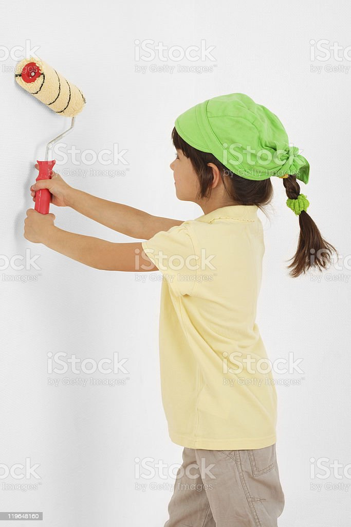 Little girl with paintroller in hands near white wall royalty-free stock photo