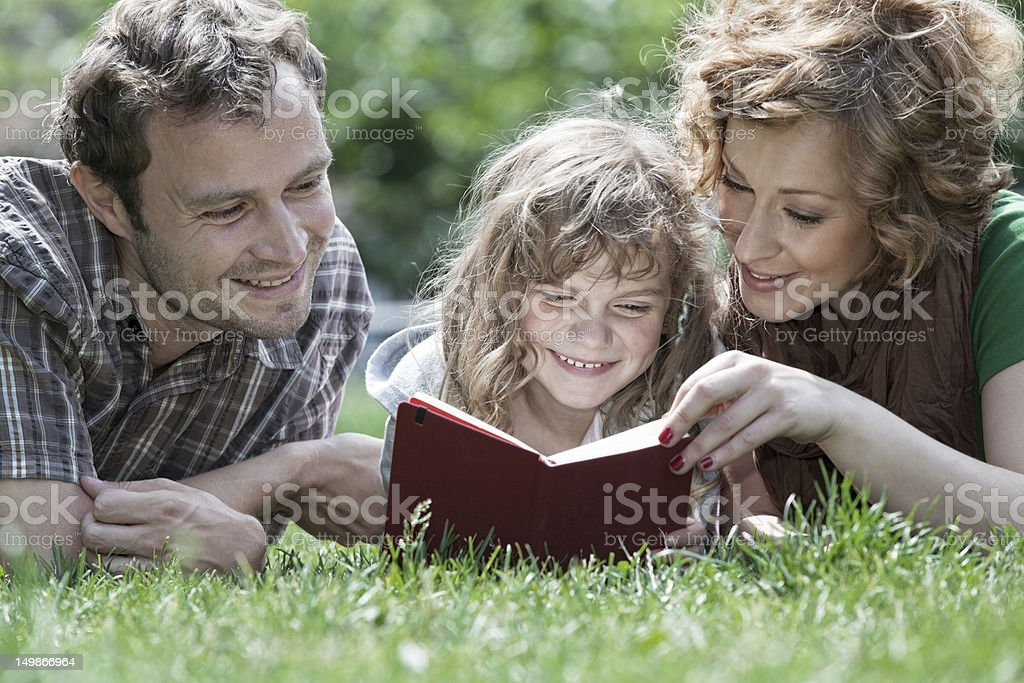 Little girl with parents lying on meadow reading book royalty-free stock photo
