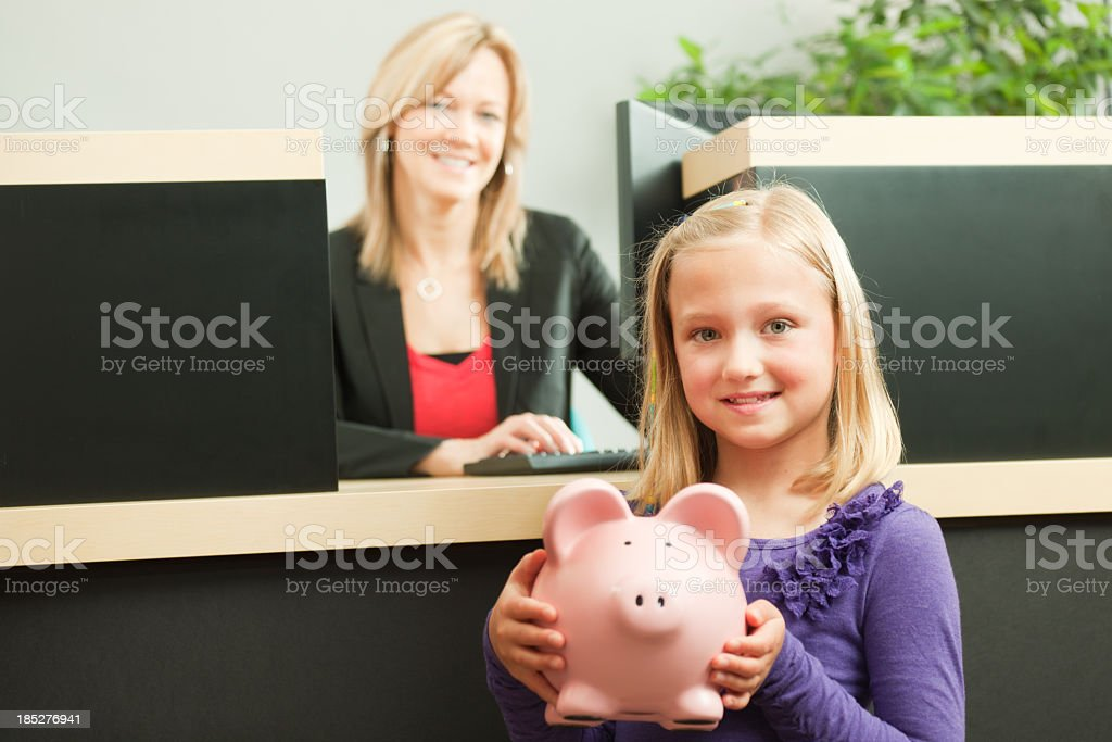 Little Girl with Piggy Bank at Teller Counter royalty-free stock photo