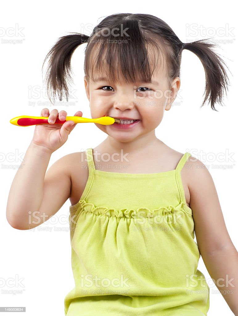 A little girl with pigtails brushing her teeth stock photo