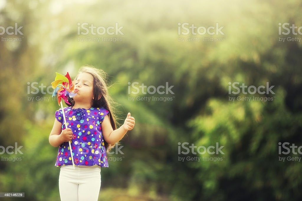 Little girl with pinwheel in the field in summer stock photo
