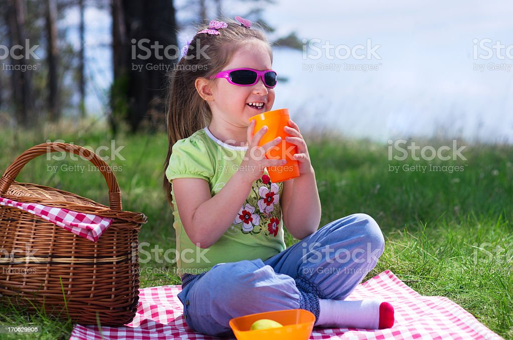 Little girl with plastic cup and picnic basket royalty-free stock photo