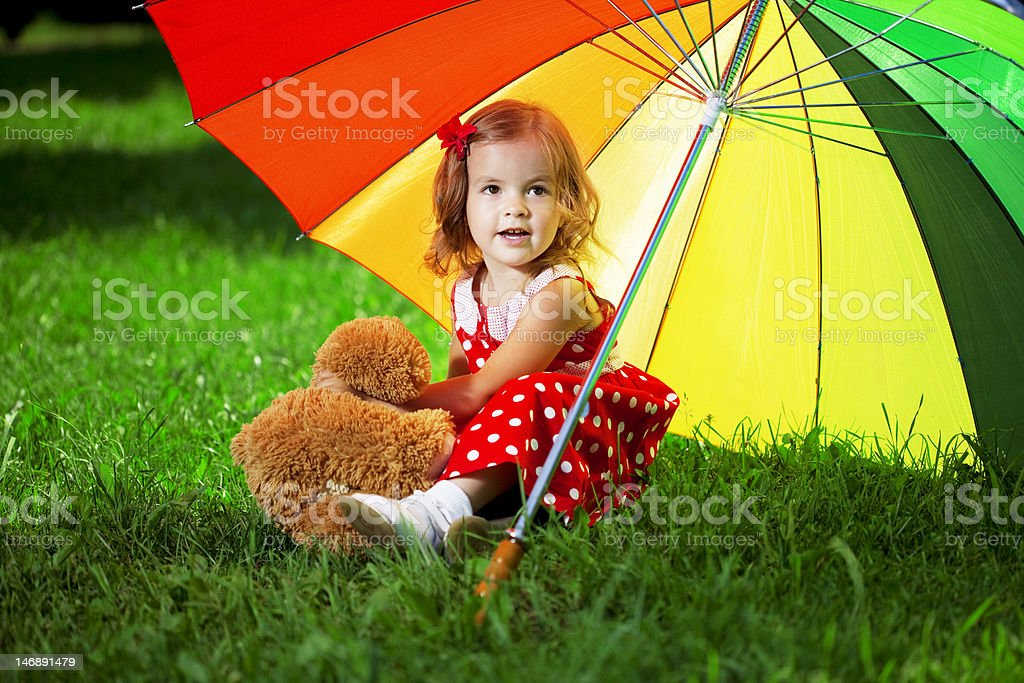 Little girl with  rainbow umbrella in park royalty-free stock photo