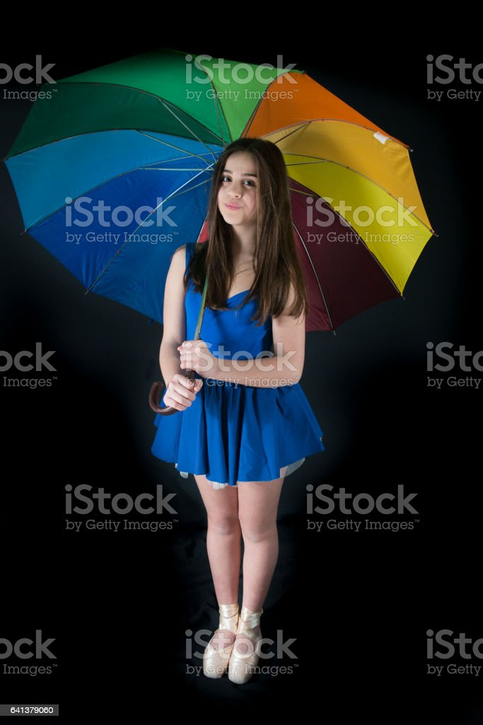 Little Girl With Rainbow Umbrella on Black Background stock photo