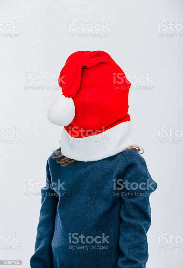 Little Girl with Red Christmas Hat Over Face stock photo