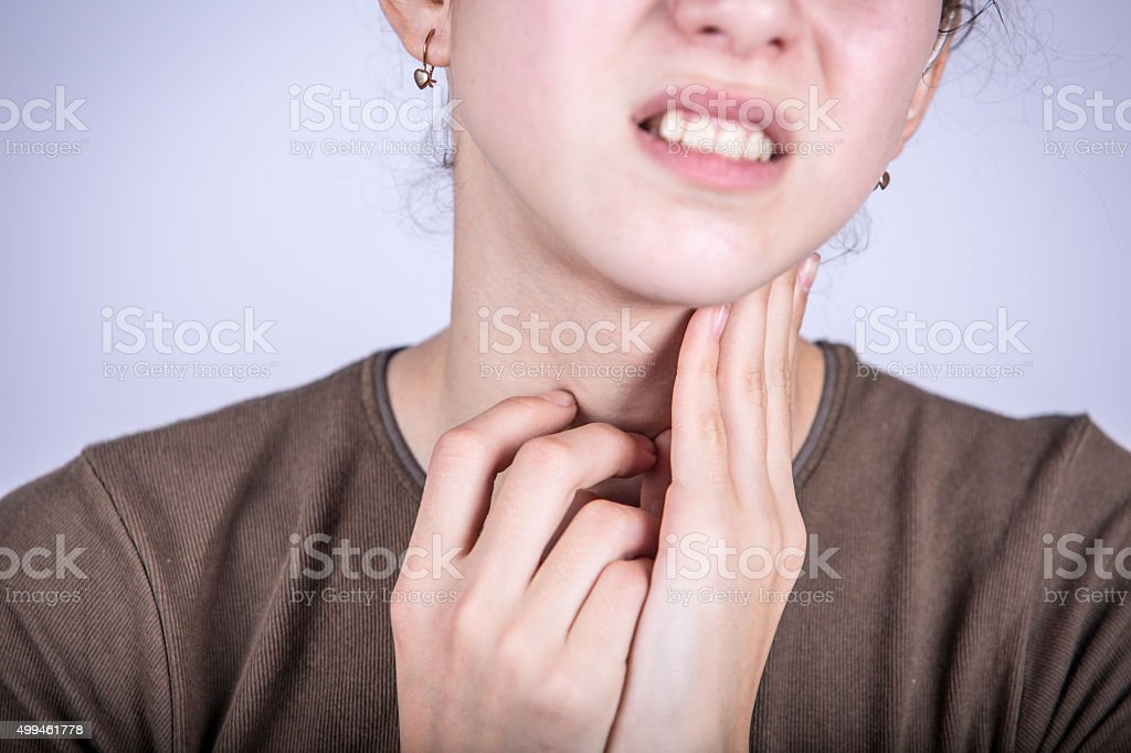 Little girl with sore throat  touching her neck stock photo