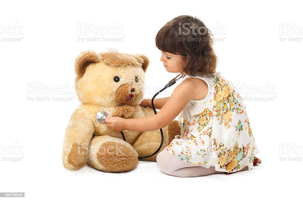 Little girl with stethoscope and  teddy bear stock photo