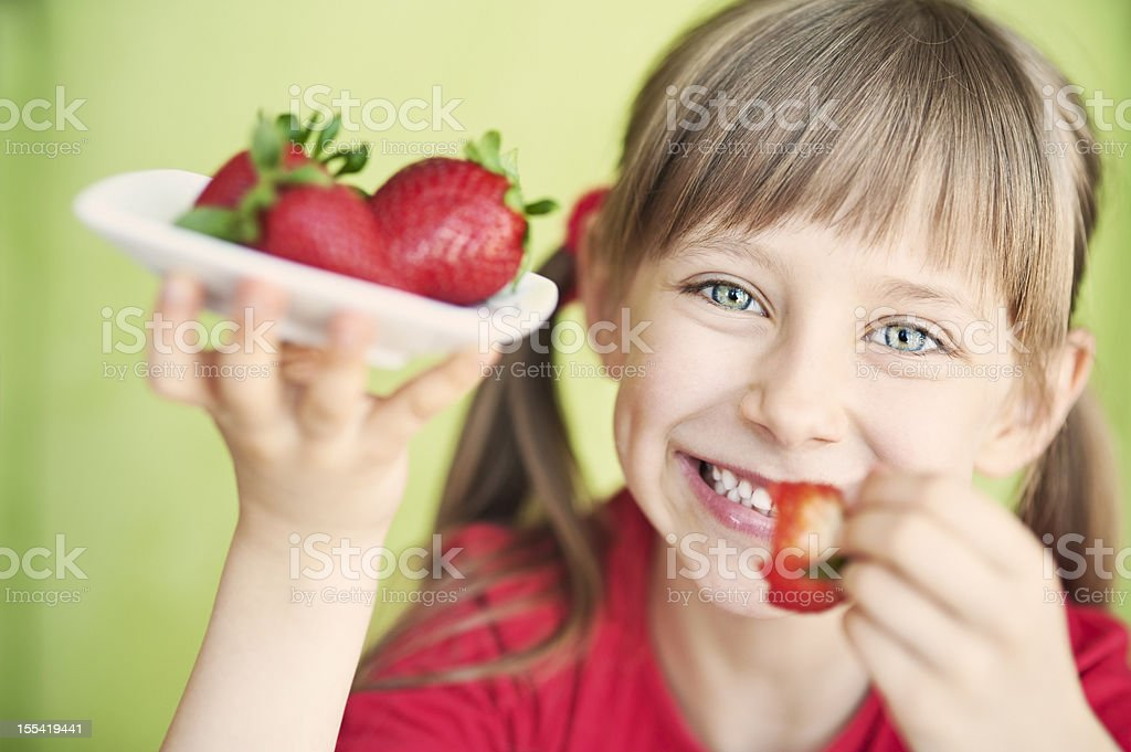 Little girl with strawberries stock photo