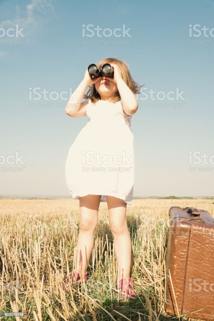 Little girl with suitcase is looking trough binoculars stock photo
