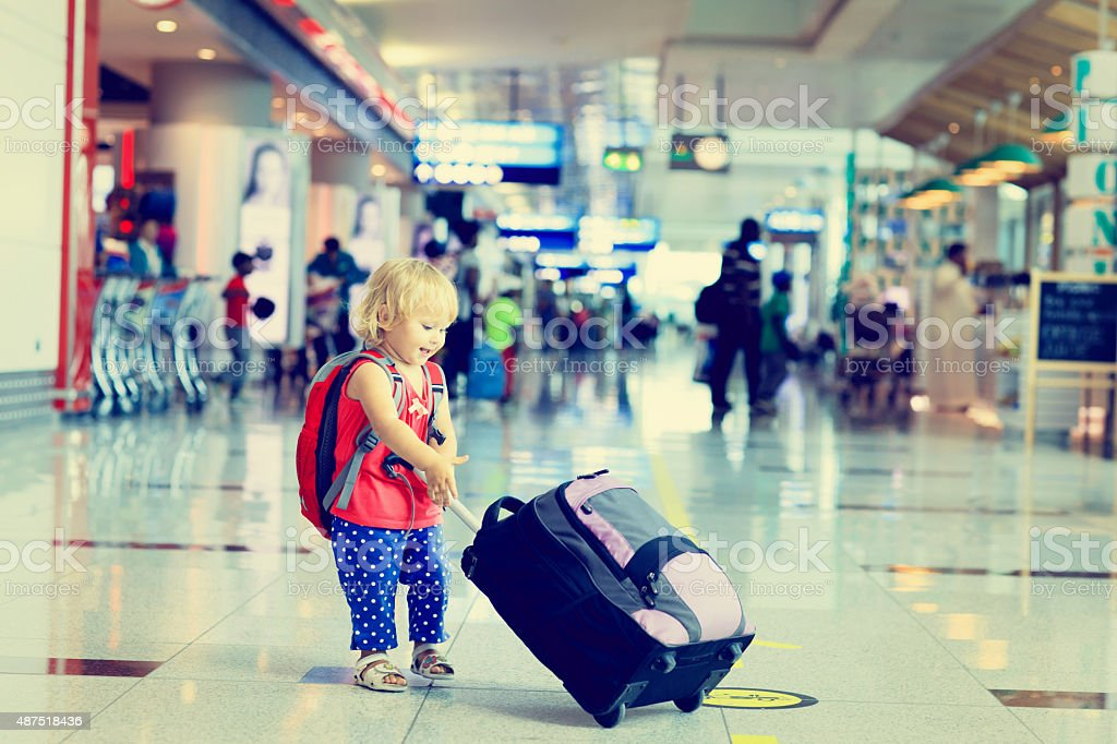 little girl with suitcase travel in the airport stock photo