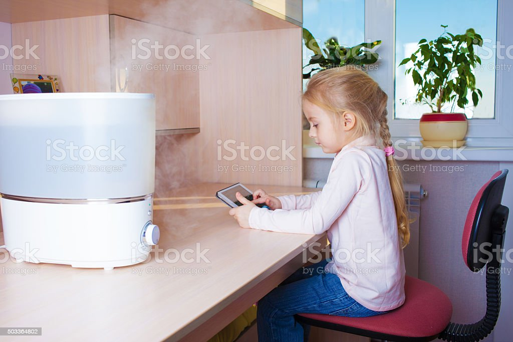 Little girl with tablet pc sitting near humidifier stock photo