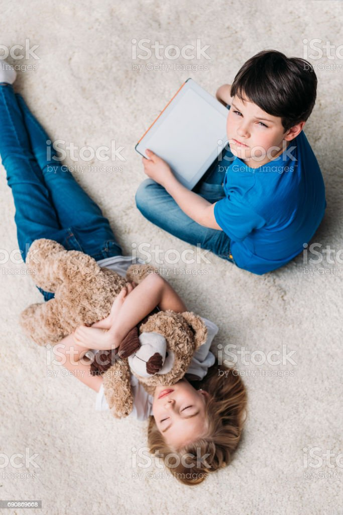 little girl with teddy bear and boy with digital tablet on carpet at home stock photo