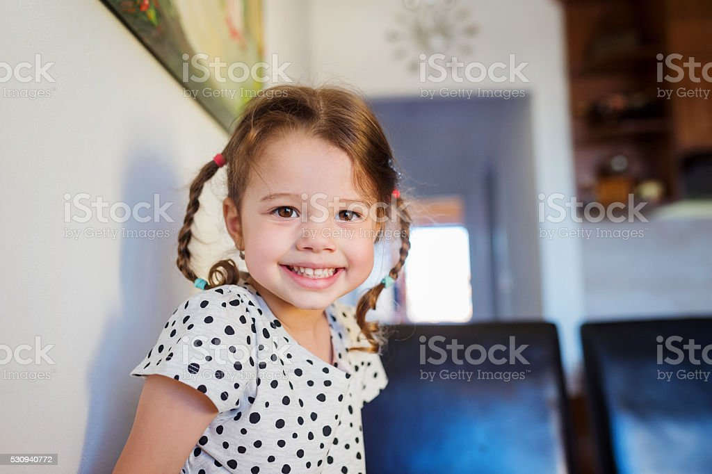 Little girl with two braids in dotted t-shirt smiling stock photo
