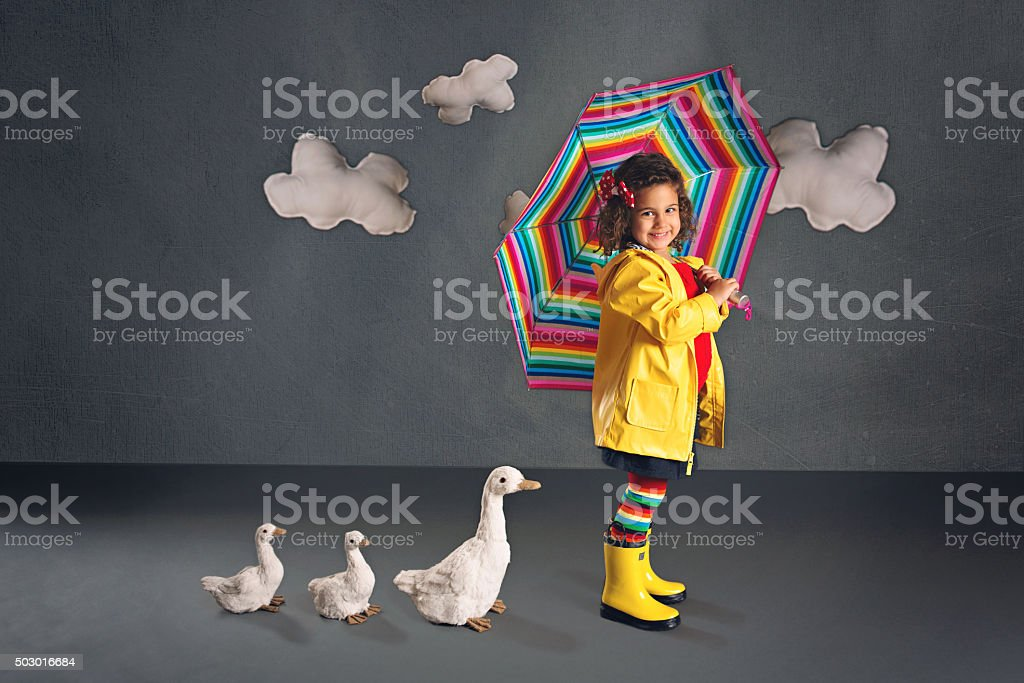 Little Girl with Umbrella and Ducks stock photo