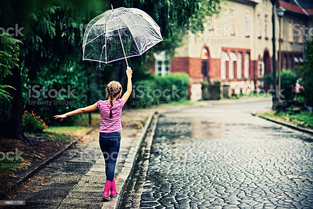 Little girl with umbrella walking in rain. stock photo