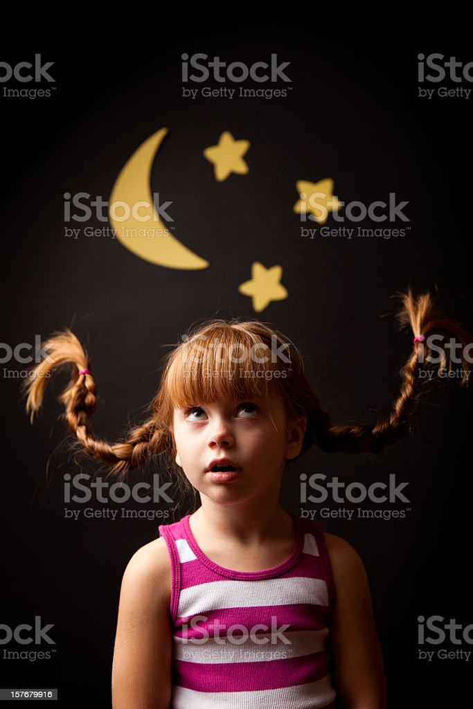 Little Girl with Upward Braids Looking at Moon and Stars stock photo