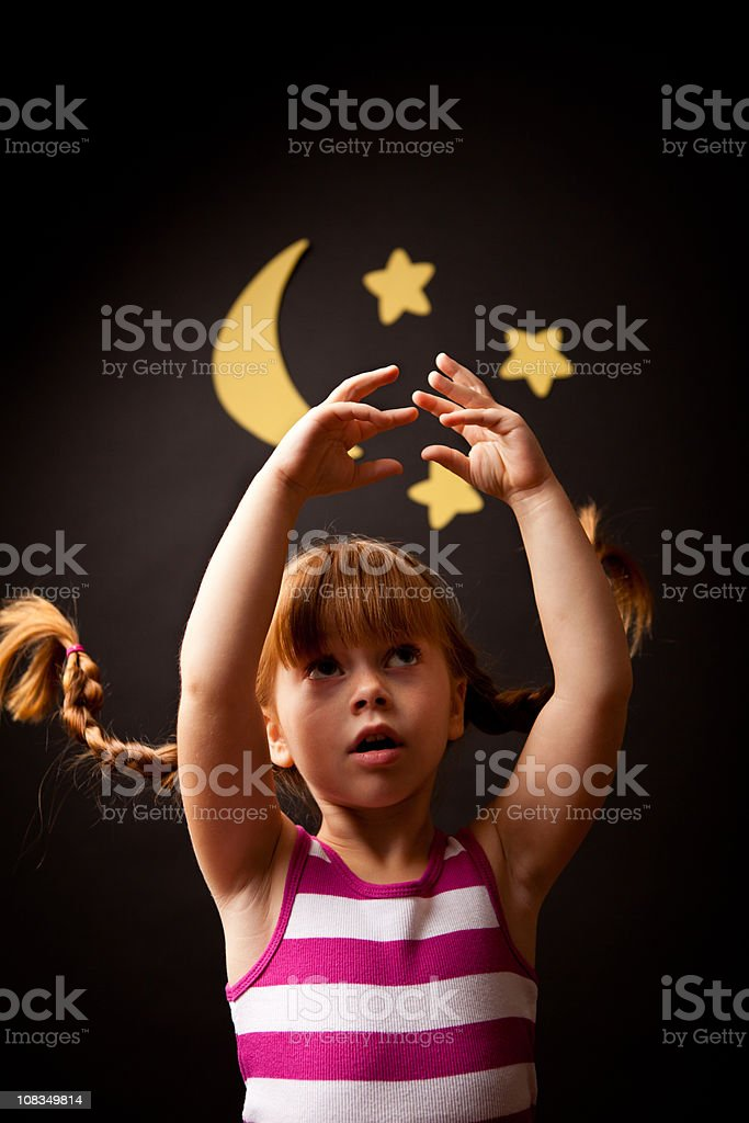 Little Girl with Upward Braids Reaching for Moon and Stars stock photo