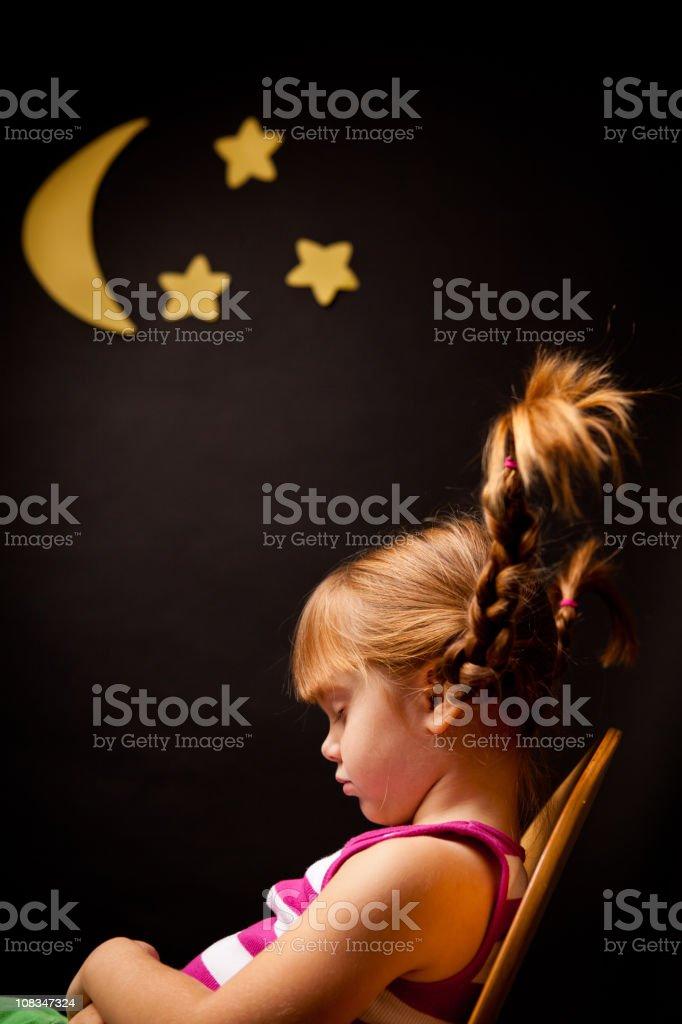 Little Girl with Upward Braids Sleeping Under Moon and Stars stock photo