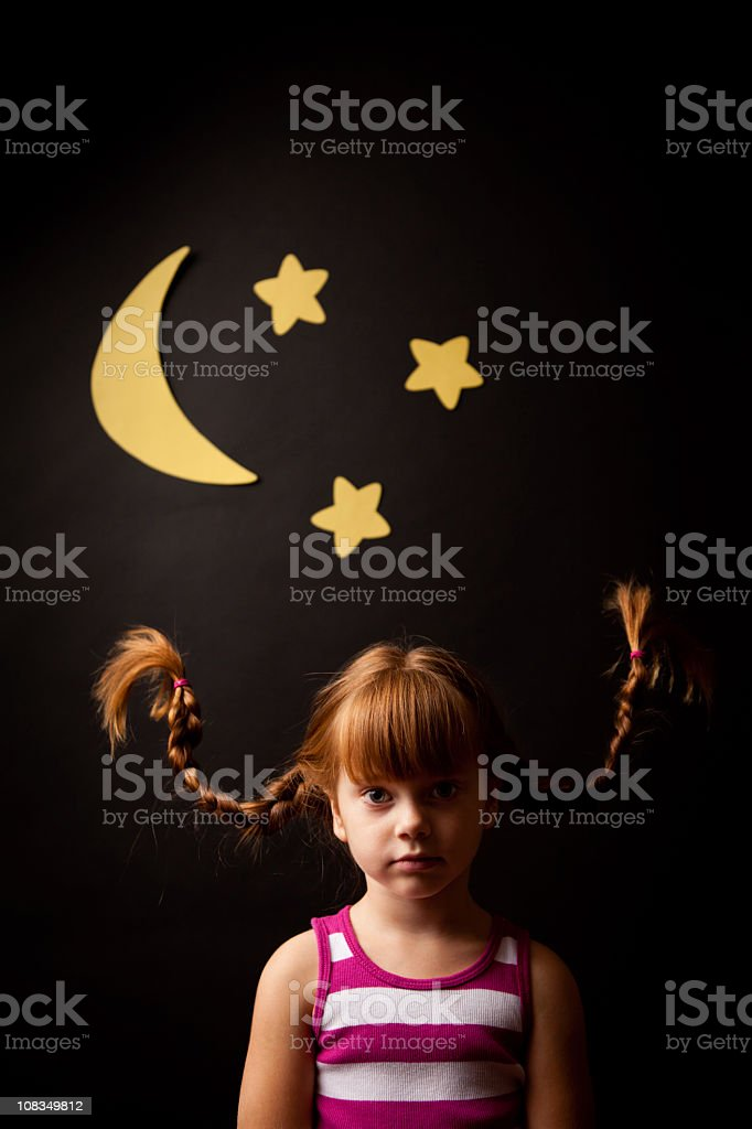 Little Girl with Upward Braids Standing Under Moon and Stars stock photo