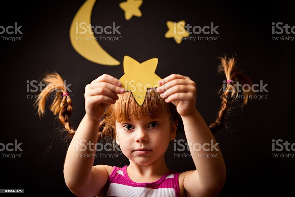 Little Girl with Upward Braids Standing Under Moon Holding Star stock photo