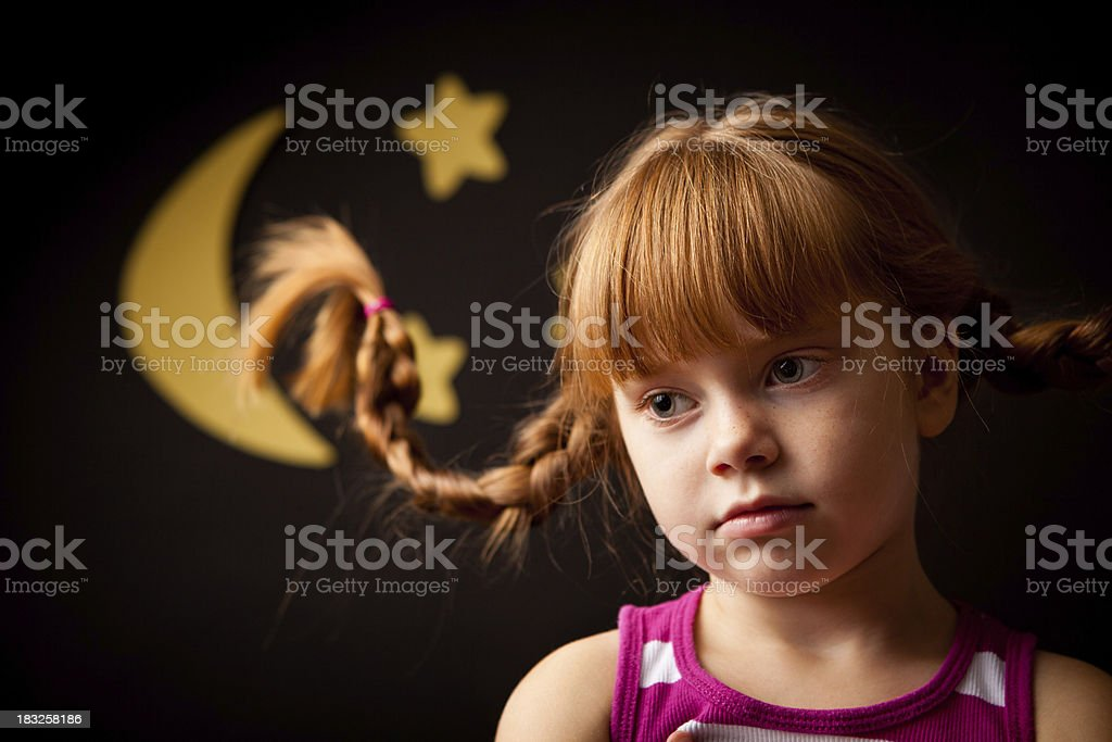 Little Girl with Upward Braids Thinking Under Moon and Stars royalty-free stock photo