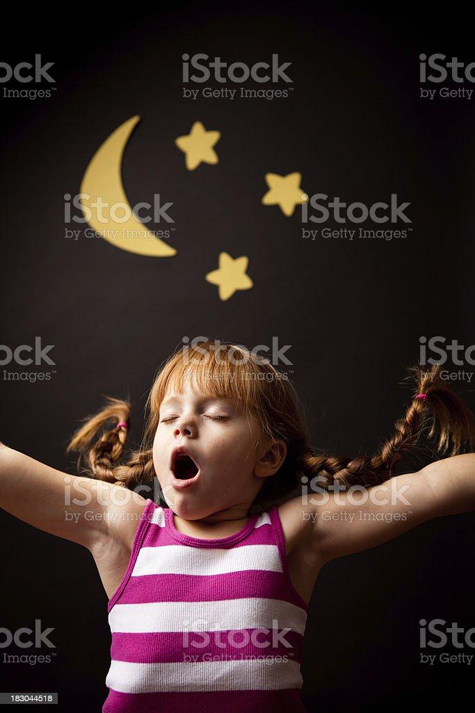 Little Girl with Upward Braids Yawning Under Moon and Stars stock photo