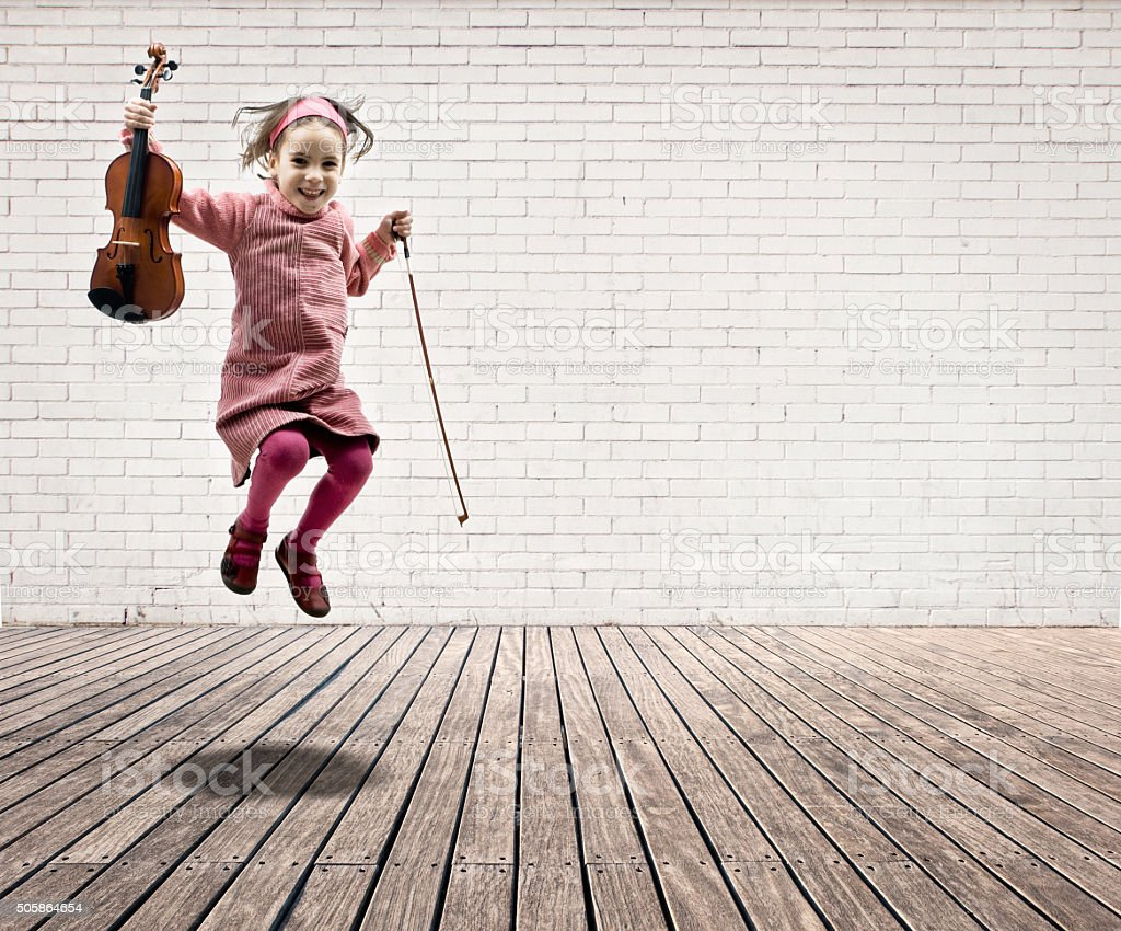 little girl with violin jumping stock photo